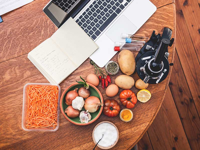 fruits and vegetables on a table with a laptop, microscope and test tubes
