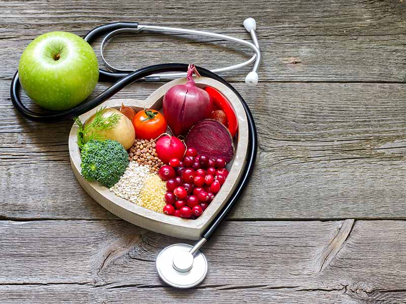 nutritious foods inside a heart container, surrounded by a stethoscope